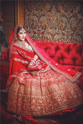 Bride sitting on sofa in bright red and gold lehenga