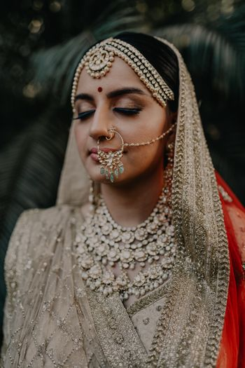 bride showing off her nath and her necklace