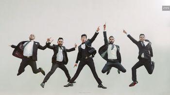 Groom jumping with groomsmen