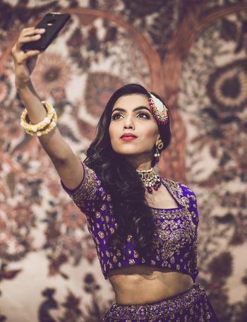 Bride in purple lehenga taking a selfie