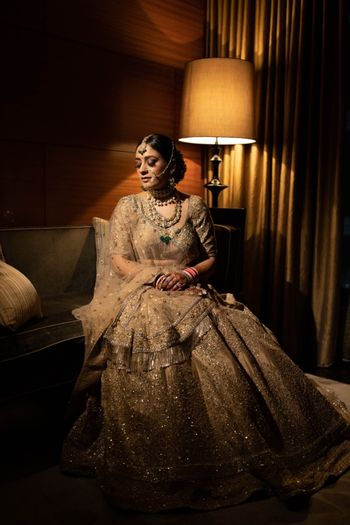 Photo of Bride dressed in a gold lehenga.
