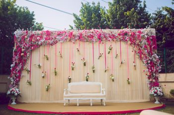 Unique engagement stage decor idea with florals in hanging bottles