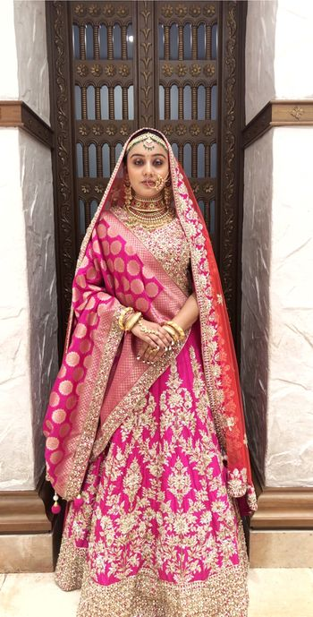 A bride in pink lehenga with a banarasi dupatta