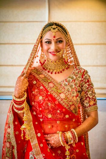Photo of Bride in red lehenga and gold jewellery