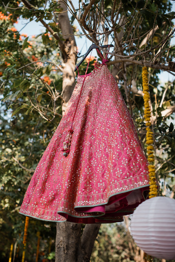 Lehenga photography with bright pink one on hanger