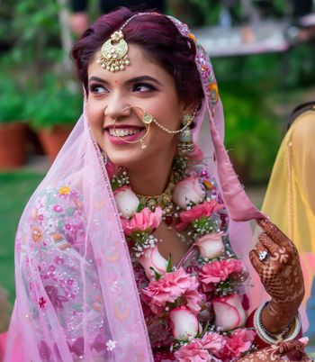 Candid shot of a bride wearing pink lehenga with green enameled jewellery.