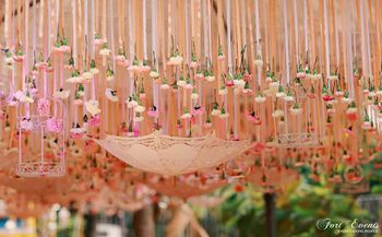 Beautiful peach decor with suspended umbrella and bird cage for mehendi