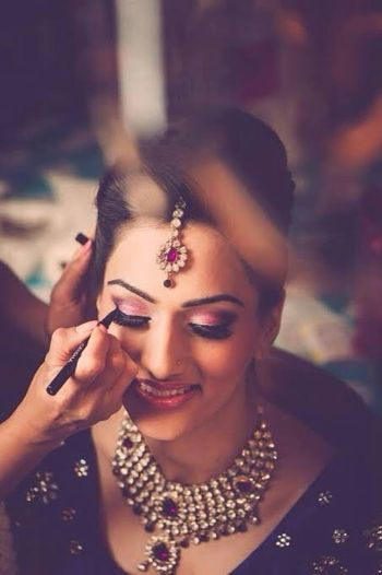 MUA putting eyeliner on bride