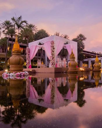 Light pink mandap with drapes by seaside