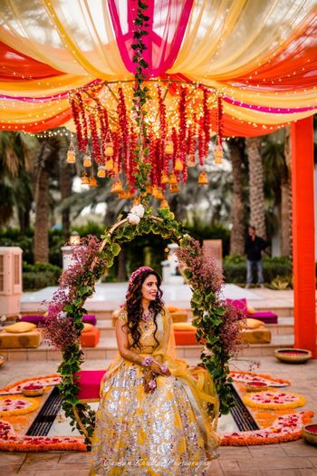 Bridal mehendi seat decor idea with bride in yellow lehenga