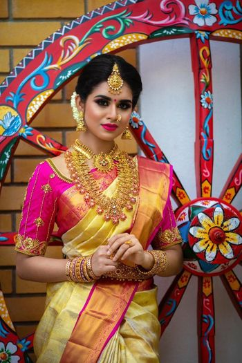 Photo of South Indian bride wearing yellow saree with a pink blouse