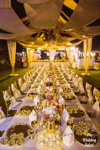 Photo of gold jugs with flower arrangements in table setting