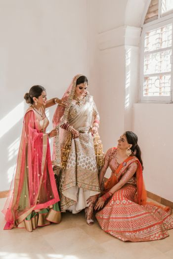 Bride in ivory with sisters helping her