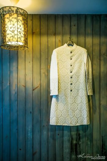 Beige sherwani on hanger on wooden wall