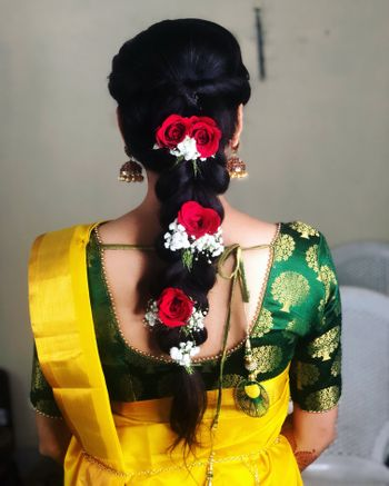 Braided hairstyle with red roses and baby breath.