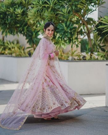 Twirling shot of a bride dressed in light pink lehenga