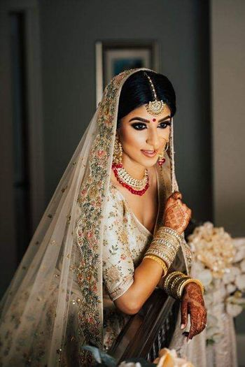 A bride in a nude floral lehenga poses on her wedding day