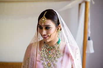 A bride in a light pink outfit getting ready