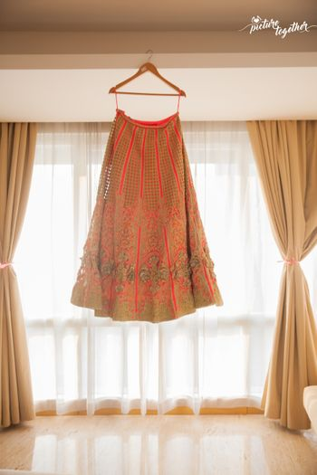 Red Lehenga with Gold Work on Hanger Against Window