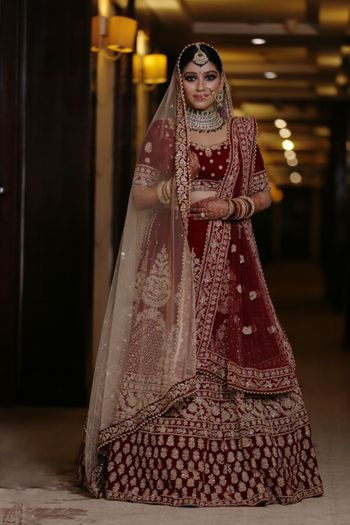 A beautiful bride in a stunning dark red lehenga and subtle makeup.