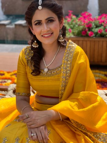 A bride in a yellow outfit and nude makeup for her mehndi ceremony