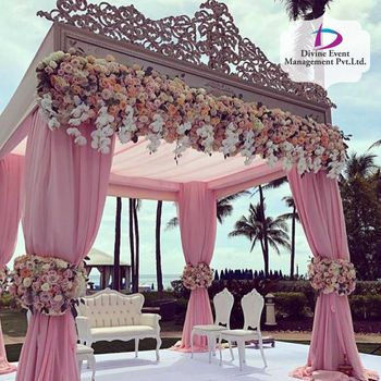 A light pink curtained mandap with floral decor