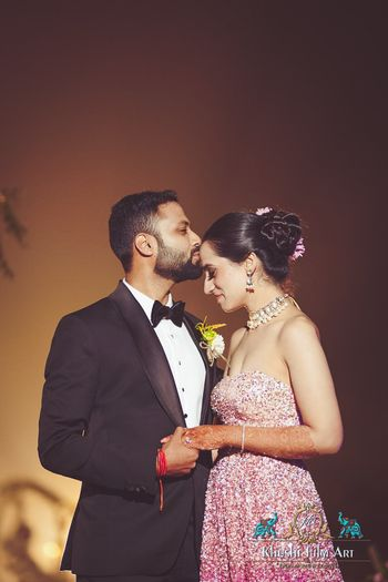 A groom kissing his bride on her forehead