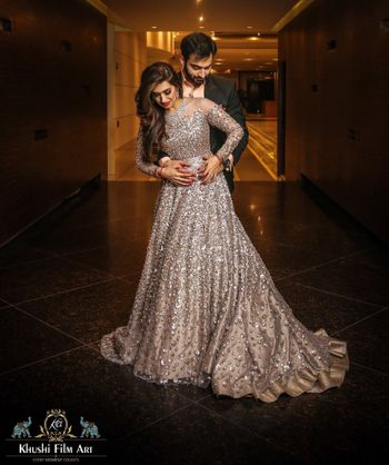 A bride in a shimmery silver gown with her to-be-husband