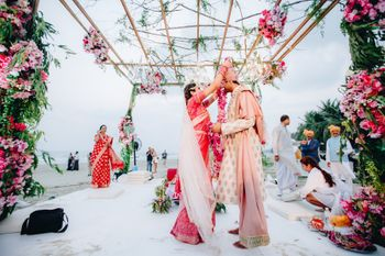 A bride and groom exchange varmalas in a floral mandap