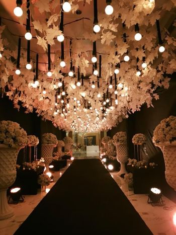 Suspended bulbs and floral strings for entrance decor.