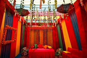 A colorful mehndi decor with inverted umbrellas, drapes and suspended flowers