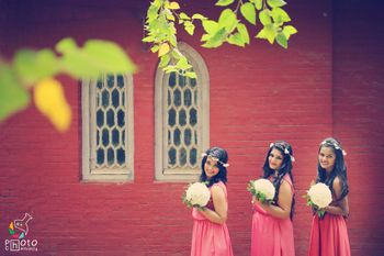 Coordinated bridesmaids in pink gowns and floral hair wreaths