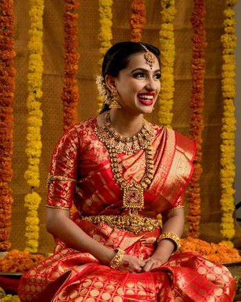 Photo of A south Indian bride in a jewel-tone kanjeevaram and stunning temple jewellery