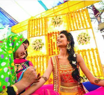 Bride getting her mehendi put against yellow backdrop