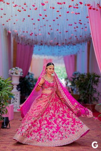 Happy bride twirling in a floral pink lehenga