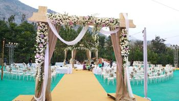 Wooden entrance decorated with flowers and drapes.