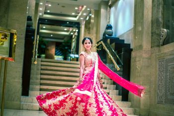 Bride twirling in pink lehenga with large gold pattern