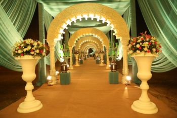 Archway entrance decor with floral vases and drapes.