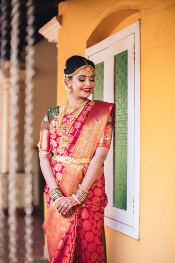 A south Indian bride in a kanjeevaram saree and gold jewelry for her wedding day