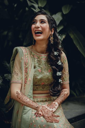A happy bride wearing a side braid with baby's breaths.