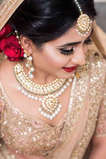 Shimmery gold lehenga on the bride with red roses in hair