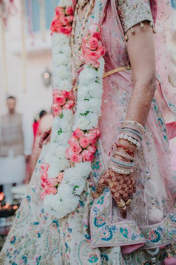 Photo of Bridal close up shot in pastel lehenga and jaimala