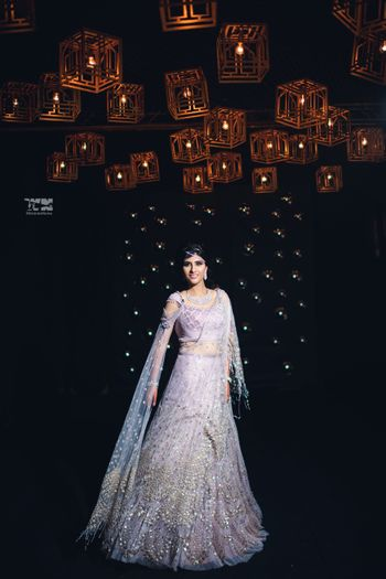 Bride wearing white lehenga with sequins work.