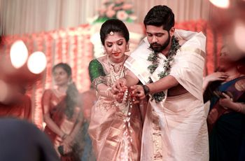 A south indian bride in a gold kanjeevaram performing wedding rituals with the groom