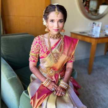 South Indian bride in a pink and dull gold saree.