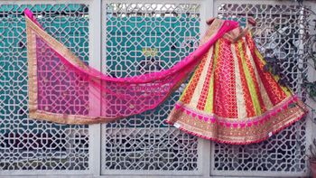 Photo of Pink, Yellow and White Lehenga on a Hanger