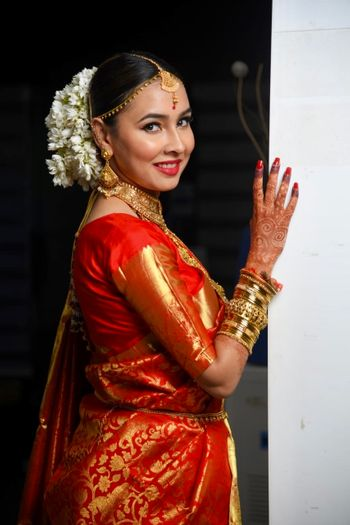 Photo of A bride in an orange banarasee saree with gajra in her hair