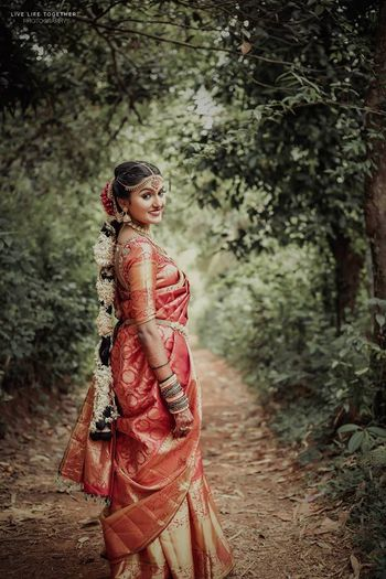 A south Indian bride in a red kanjeevaram with gajra in her hair