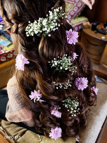 Half up half down hairstyle with baby's breaths and lavender flowers.