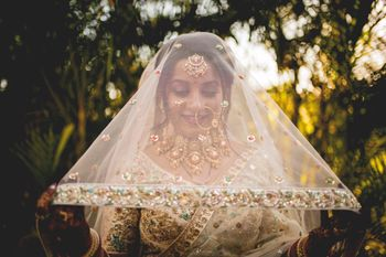 bride holding her gold and ivory dupatta as veil